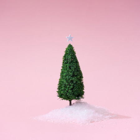 Christmas tree with snow on pastel pink background. Minimal holiday concept. New year simple composition. Merry Christmas and happy New Year greeting card. Stock Photo