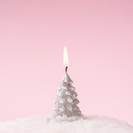 Christmas tree candle with snow on pink background with copy space. Minimal flat lay Christmas theme. New year sale concept. Stock Photo