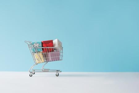 Einkaufswagen voll mit Geschenkboxen. Minimales Konzept.