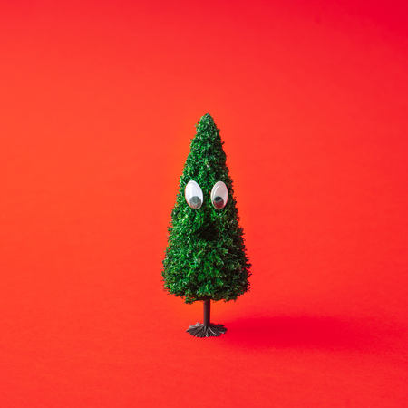 Christmas tree with googly eyes on red background. Minimal New Year fun concept.