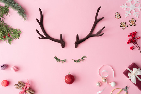 Christmas reindeer concept with presents, decoration, and winter things on pastel pink background. Minimal winter holidays idea. Flat lay top view composition. Stock Photo