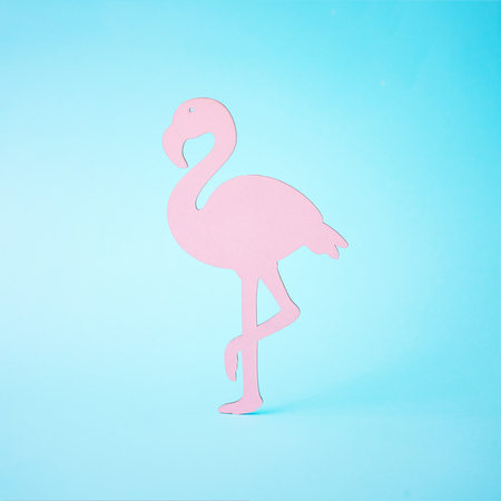Pink flamingo shape on bright blue background. Summer tropical composition with copy space. Flat lay minimal. Summer Holiday layout.