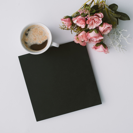 Creative winter natural composition with flowers and coffe cup. Flat lay, table top view. Greeting card copy space.