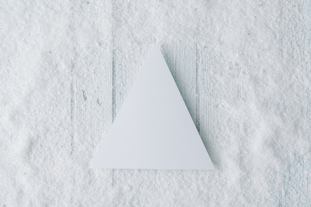 Snowy Christmas background composition with paper card note. Flat lay. Top view.
