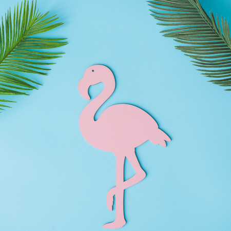 Pink flamingo shape with green tropical leaves on bright blue background. Summer tropical composition with copy space. Flat lay minimal. Summer Holiday layout.