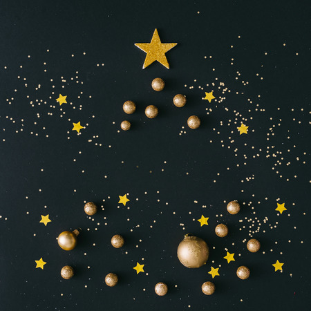 Golden Christmas tree background on black table. New Year card. Flat lay. Top view. Stock Photo