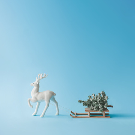 Santa Clauss Reindeer pull a sleigh with Cristmas tree. Minimal New Year concept. Creative winter holiday idea.