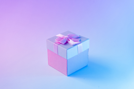 Gift box in vibrant bold gradient holographic colors. Christmas concept art. Minimal New Year surrealism.