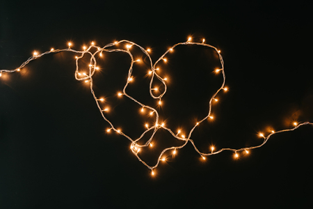 Heart shape made of Christmas lights decoration on dark background. New Year flat lay background. Imagens