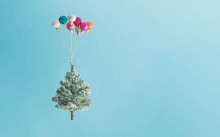 Christmas tree lifted up by colorful balloon ornaments against sky blue background. New Year concept.