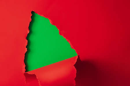 Christmas tree shape made with red and green paper. Minimal Christmas background. with copy space.