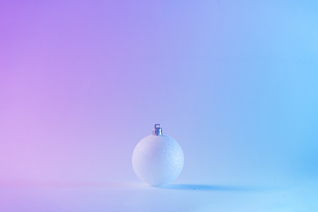 White Christmas ball in vibrant bold gradient holographic colors. Concept art. Minimal New Year surrealism.