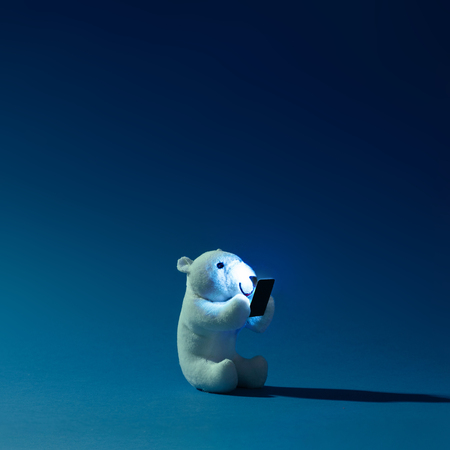 Polar bear toy with mobile phone on night blue background. Winter concept.