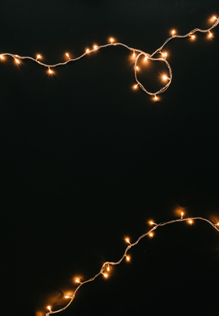 Christmas lights decoration on dark background. New Year flat lay background.
