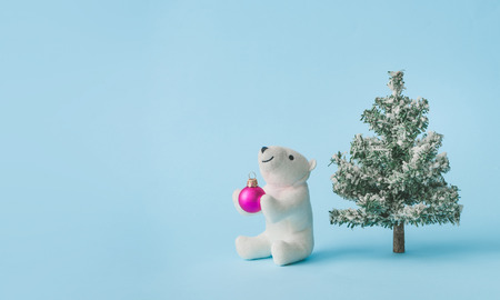 Polar bear toy with Christmas tree and ball ornament on bright pastel blue background. Christmas and winter holidays concept. Imagens