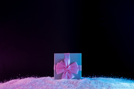 Gift box on snow in vibrant bold gradient holographic colors. Christmas concept art. Minimal New Year surrealism.
