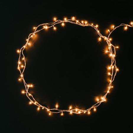 Round shape made of Christmas lights decoration on dark background. New Year flat lay background. Imagens