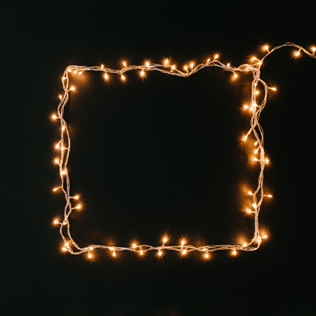 Square shape made of Christmas lights decoration on dark background. New Year flat lay background.