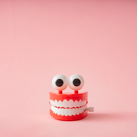 Plastic toy teeth against pastel background. Abstract minimal composition. 版權商用圖片