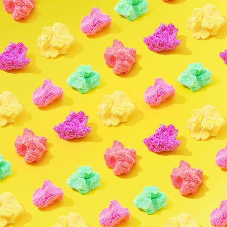 Colorful slime pattern on bright yellow background. Minimal creative art concept.