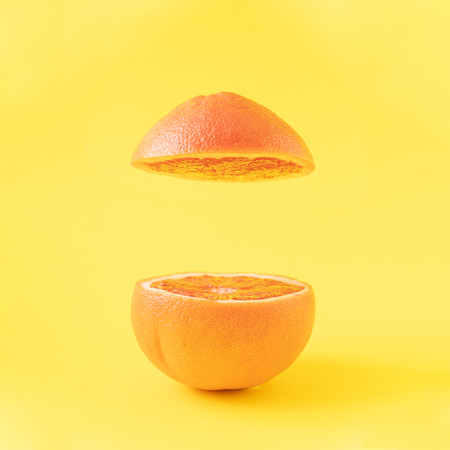 Sliced red grapefruit with creative copy space on bright yellow background.
