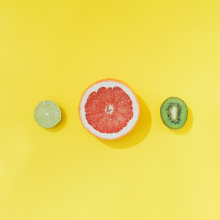 Tropical fruit on pastel yellow backround. Minimal summer food concept. Imagens