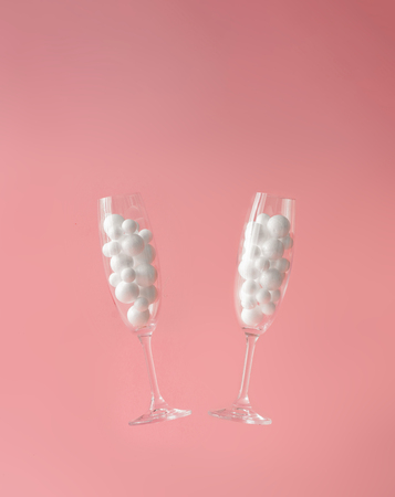 Pair of champagne glasses with white bubbles with pastel background. Minimal party idea.