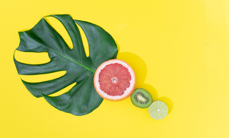 Monstera leaf with tropical fruit on bright yellow background. Minimal summer concept.