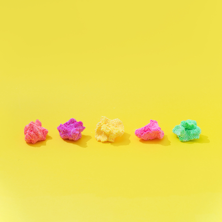Colorful slime on bright yellow background. Minimal creative art concept.