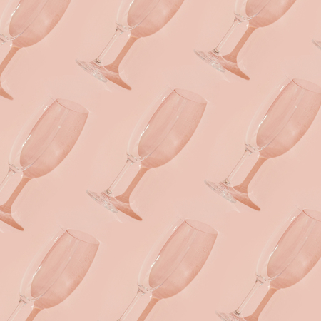 Minimal style. Champagne glasses on pastel coral background.