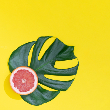 Monstera leaf with Red grapefruit on bright yellow background. Minimal summer concept.