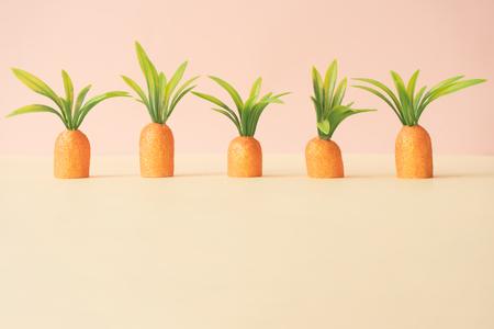 Carottes sur jaune pastel. Concept de Pâques minimal. Composition minimale de printemps.