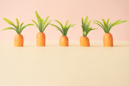 Carrots on pastel yellow. Minimal Easter concept. Spring minimal composition.