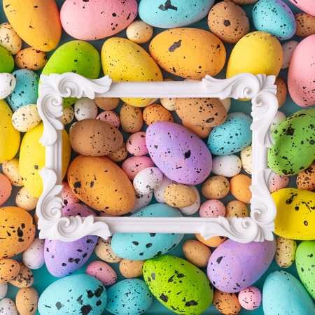 Easter composition made with colorful eggs and vintage frame. Creative holiday concept. Imagens