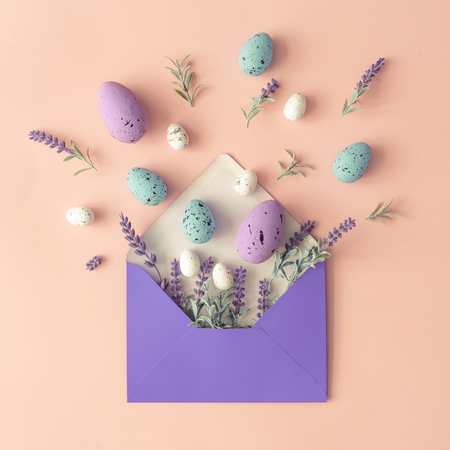 Creative layout made with spring flowers, leaves and Easter eggs on pastel pink background and paper envelope. Minimal holiday composition with copy space. Imagens
