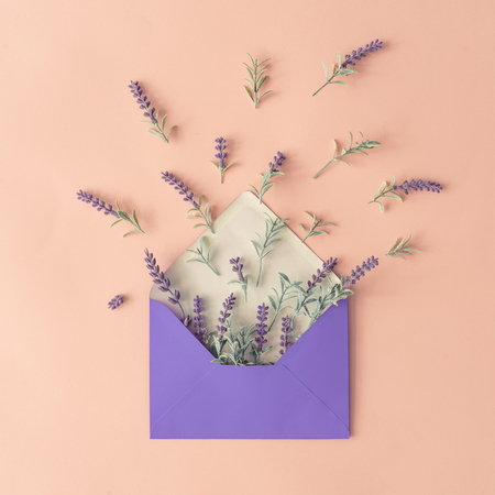 Creative layout made with spring flowers and leaves on pastel pink background and paper envelope. Minimal nature composition with copy space.