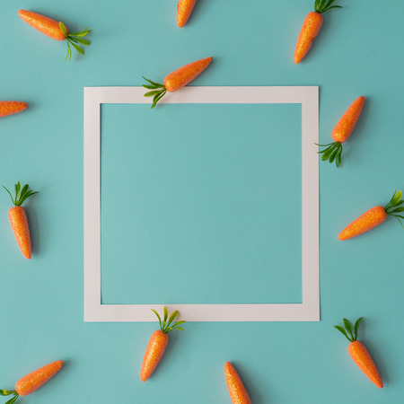 Easter pattern made with carrots on bright blue background. Creative minimal holiday concept. Imagens