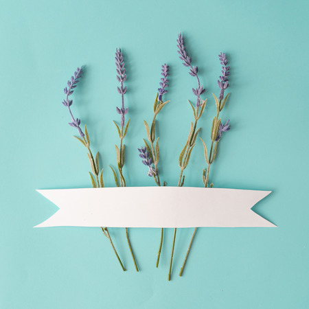 Spring composition made with lavander flowers on bright blue background with ribbon copy space. Creative minimal holiday concept. Flat lay.