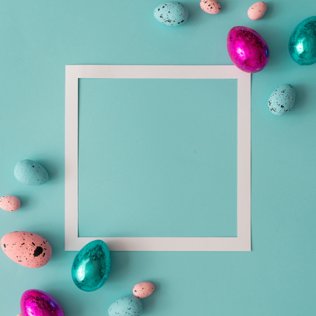 Easter composition made with colorful eggs on bright blue background. Creative minimal holiday concept. Flat lay. Imagens