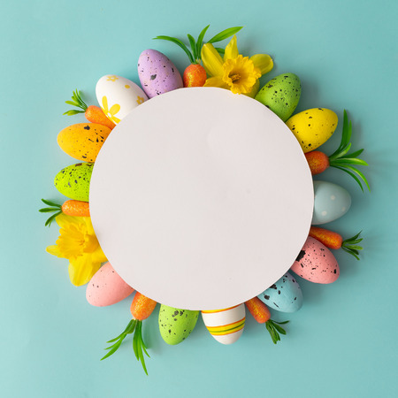 Creative composition made with colorful Easter eggs and spring flowers and paper card copy space. Minimal holiday background.