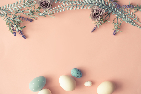 Creative layout made with spring flowers leaves and Easter eggs on pastel pink background. Minimal nature composition.
