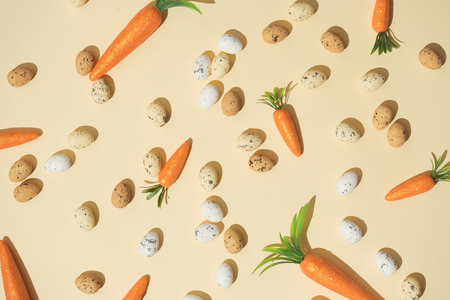 Easter eggs and carrots on pastel yellow background. Easter holiday concept. Minimal composition. Imagens