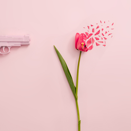Creative concept made with pink gun and red tulip flower exploding on pastel pink background. Minimal nature composition with copy space.