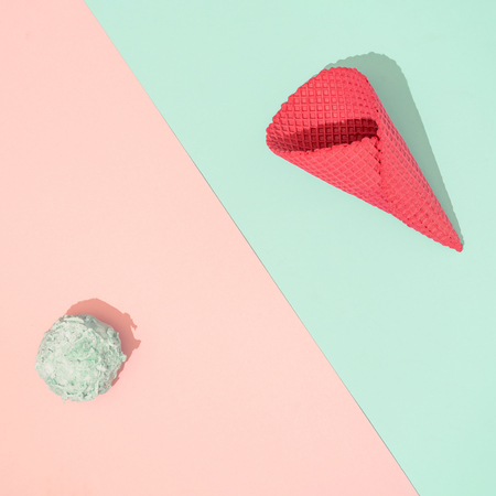 Ice cream cone with scoop of ice cream on pastel pink and blue background. Minimal summer food concept. Flat lay.