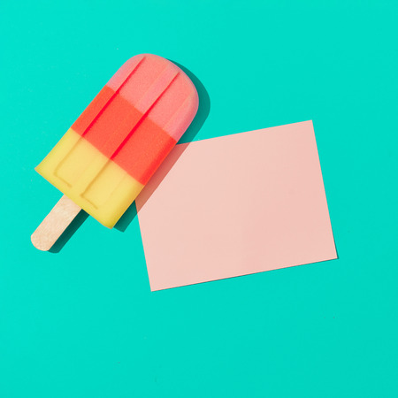 Ice cream with pink paper card note on vivid blue background. Minimal summer composition. Flat lay.