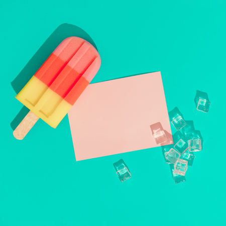Ice cream with ice cubes and pink paper card note on vivid blue background. Minimal summer composition. Flat lay. Imagens