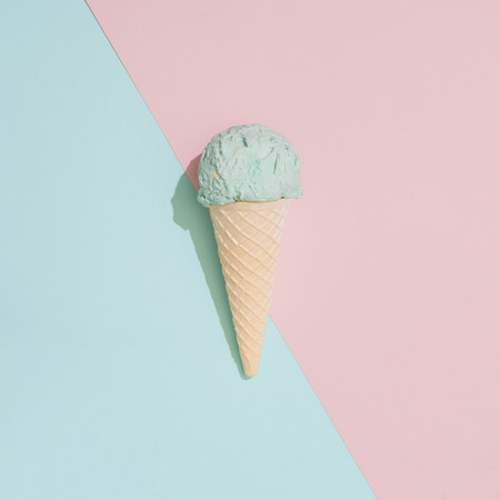 Ice cream on pastel pink and blue background. Minimal summer food concept. Flat lay.