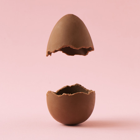 Chocolate Easter egg broken in half on pastel pink background with creative copy space. Minimal Easter holiday concept. Stockfoto