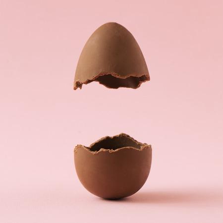Oeuf de Pâques au chocolat cassé en deux sur fond rose pastel avec espace de copie créative. Concept minimal de vacances de Pâques.
