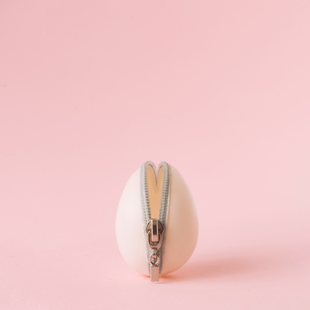 Easter egg with zipper on pastel pink background. Creative minimal concept. Imagens
